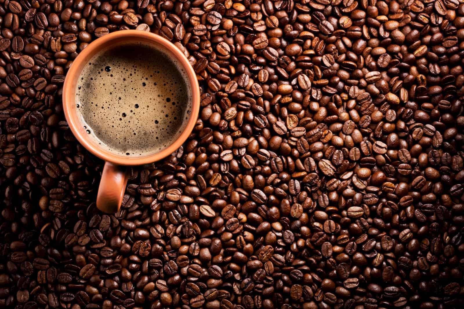 grãos de café com xícara